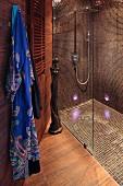 Duschbereich mit Glastrennscheibe, braunen Mosaikfliesen an Wand und Boden, seitlich aufgehängter Morgenmantel im Designerbad