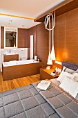 Elegant bed against wood-clad wall and designer pendant lamps in bedroom with ensuite bathroom