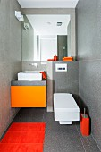 Designer-style guest toilet with grey-tiles walls and various orange accents