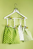 Fabric bags in shades of green hanging from clothes hanger