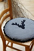 Round cushion made from blue and white gingham cotton decorated with pompom trim and stag's head appliqué
