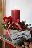 Brennende Kerze mit weihnachtlichem Gesteck in einer Keramikschale, Zinkschild und Geschenkband mit Weihnachtsgruß