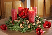 Classic Advent wreath with branches or fir and thuja, walnuts, amaryllis flowers and red candles