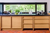 Modern kitchen counter with wooden base units and black worksurface below ribbon window with view of trees