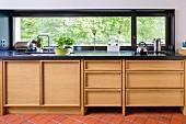 Moderne Küchenzeile mit Holzeinbauten unter schwarzer Platte, vor Fensterband mit Aussicht