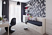 Black and white child's bedroom with floral wallpaper and classic chair