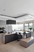 Multifunctional, designer kitchen; breakfast bar with bar stools, attached low sideboard and pendant lamps hanging from suspended ceiling elements