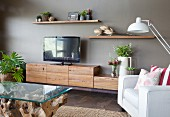 Coffee table with glass top, pale armchair and low sideboard with rustic, wooden cupboards on grey wall
