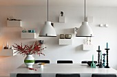 Industrial-style pendant lamps above branches of berries in vase of candlesticks on dining table in front of ornaments on small bracket shelves