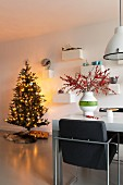 Brightly lit Christmas tree and upholstered chair in dining area in modern interior