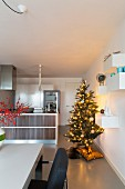 Brightly lit Christmas tree in modern, open-plan kitchen