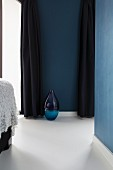 Blue glass floor vase on white epoxy resin floor beteen dark blue, floor-length curtains
