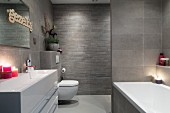 Elegant bathroom with grey wall tiles of various formats and lit candles on washstand with trough-style sink