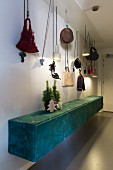 Christmas arrangement on floating sideboard covered in patterned fabric below bags and hats hung from ropes