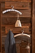 Clothes hangers covered in patterned fabric hanging from rustic coat racks