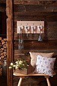 Hand-made key rack with love-hearts on wooden wall above cushions and bouquet on stool