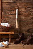 Shoe horn with hand-made handle hung on wooden wall above laced walking boots and footstool