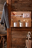 Metal containers covered in toile de jouy fabric attached to hand-made pinboard