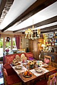 Place settings on rustic wooden table, chairs, bench and various country-house furniture in room with wood-beamed ceiling