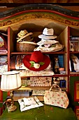 Romantic hats and decorative boxes in old, farmhouse cupboard