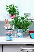 Verzierte Blechdosen als Behälter für Küchenutensilien und Kräuter