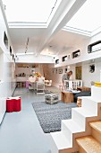 Offener, moderner Wohnraum im Hausboot mit Oberlicht in Decke, im Hintergrund Frau bei Babybett, seitlich Essplatz