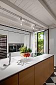 Moderne Kücheninsel mit Holzfront in rustikalem Raum unter geweisselter Holzdecke