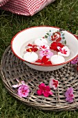 Geranium flowers and candles floating in vintage enamel bowl on wicker mat