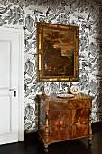Antike Kommode mit Schnitzereien und gerahmtes Gemälde vor tapezierter Wand mit floralem Mustern