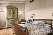Wicker sleigh bed and antique carved wardrobe in rustic bedroom