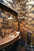 Curved washstand with silver sink, wallpaper with pattern of gold leaves and mirror with vintage frame in bathroom