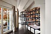 Gangbereich mit überbautem Treppenabgang aus Stellagen als Stellfläche für Bücher