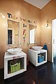 White, twin washstands with countertop basins, mirrors and motto painted on apricot wall