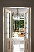Open double doors with leaded glass panels and view of elegant marble floor and dining set