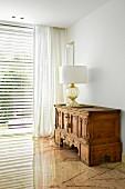 Tischleuchte mit weißem Schirm auf antikem, geschnitztem Holzschrank in Wohnzimmerecke mit Marmorfussboden