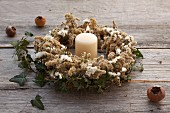 Autumn wreath of dried goldenrod, sea lavender and ivy around candle