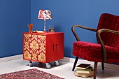 DIY minibar made from two wooden crates covered in wallpaper on castors next to 50s armchair