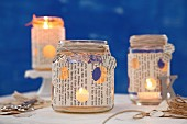 Candle lanterns hand made from old jam jars covered with book pages
