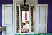 View from room with indigo wall through double doors with pale blue accents on panelling into colourful child's bedroom in background