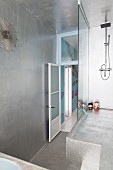 Futuristic shower platform with glass screen in silver-painted bathroom with sunburst clock