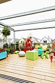 Spielendes Kind auf grosser, verglaster Dachterrasse mit Holzbelag und Pflanztöpfen zwischen farbenfroher Ausstattung