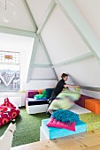 Colourful floor cushions below pastel ceiling beams of exposed roof structure