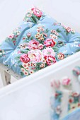Romantic, pastel-blue seat cushion with pattern of roses