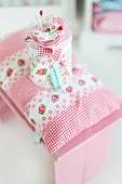 Romantic, rose-patterned stool cushion and matching tin on pink, vintage stool