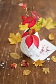 Autumnal table arrangement with yellow leaves and white vase of red leaves