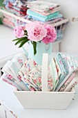 Folded, rose-patterned fabrics in pastel shades arranged in white wooden trug - vintage ambiance