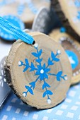 Small slice of tree trunk painted with blue and white snowflake as Christmas decoration