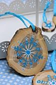 Kleine Baumscheiben als Weihnachtsdekoration, bemalt mit blau-weißem Sternenmotiv
