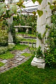Antique columns lining path and steps leading to stone bench in seating area