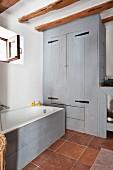 Badewanne mit hellgrau lasierter Holzfront und Einbauschrank in gleicher Optik in rustikalem Bad, mit Terrakottafliesen